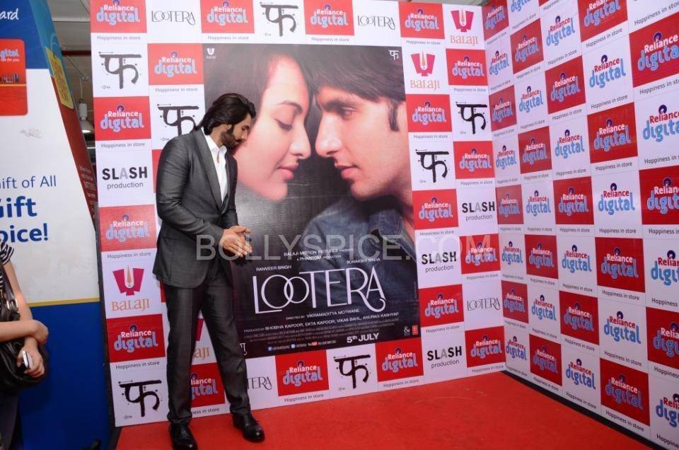 Ranveer Posing with the banner of his upcoming movie Lootera In Pictures: Ranveer Singh Visits Reliance Digital, Gurgaon to promote Lootera!