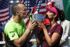 Soares of Brazil and Mirza of India kiss their trophy after defeating Gonzalez of Mexico and Spears of the U.S. in the mixed doubles final match at the 2014 U.S. Open tennis tournament in New York